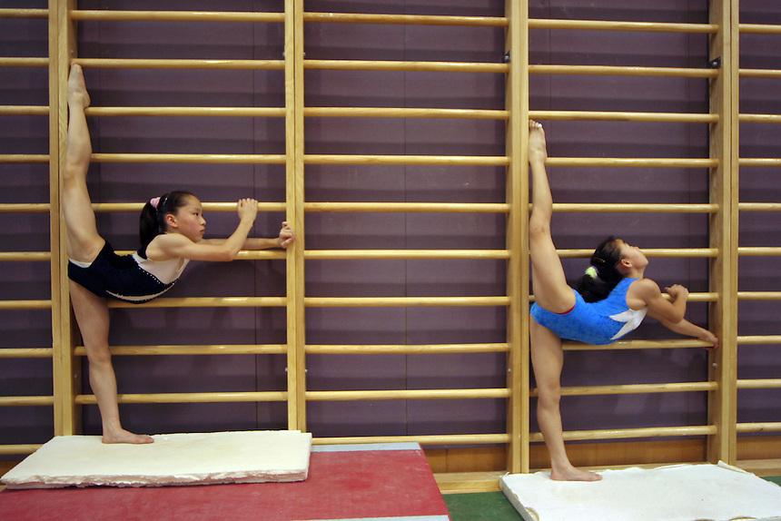 Girls on China's national gymmastics team warm up before training in Beijing.