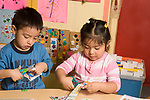 Education preschool  3-4 year olds fine motor literacy activity boy and girl cutting up catalogs and magazines horizontal