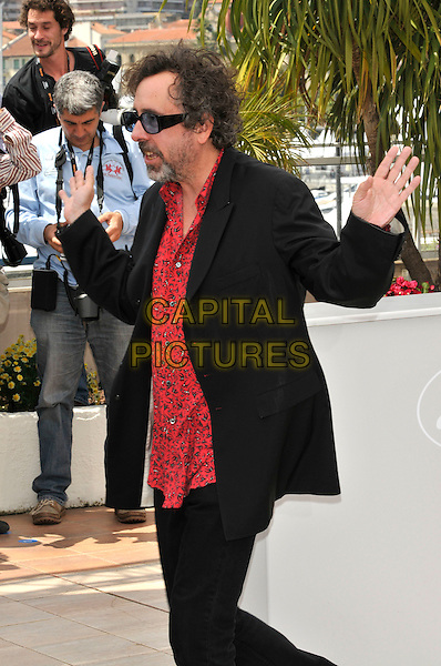 TIM BURTON.attending the Jury Photocall at the Palais des Festivals during the 63rd Annual Cannes International Film Festival, Cannes, France, 12th May 2010..half length side profile hands waving suit  red print shirt blue tinted glasses sunglasses beard facial hair .CAP/PL.©Phil Loftus/Capital Pictures.