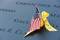 A small American flag and a yellow ribbon left on the names at the National 9/11 Memorial in New York City.
