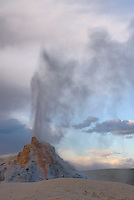 White Dome Geyser erupts in late afternoon, along the Firehole Lake Drive in Yellowstone NP
