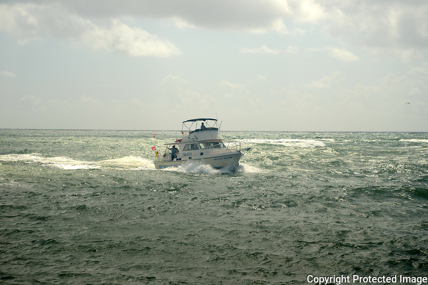 Dive boat approaching the Boynton Beach inlet on an overcast day with choppy seas.