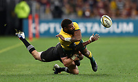 Marika Koroibete of the Wallabies gets a pass away under a tackle from Beauden Barrett of the All Blacks during the Rugby Championship match between Australia and New Zealand at Optus Stadium in Perth, Australia on August 10, 2019 . Photo: Gary Day / Frozen In Motion