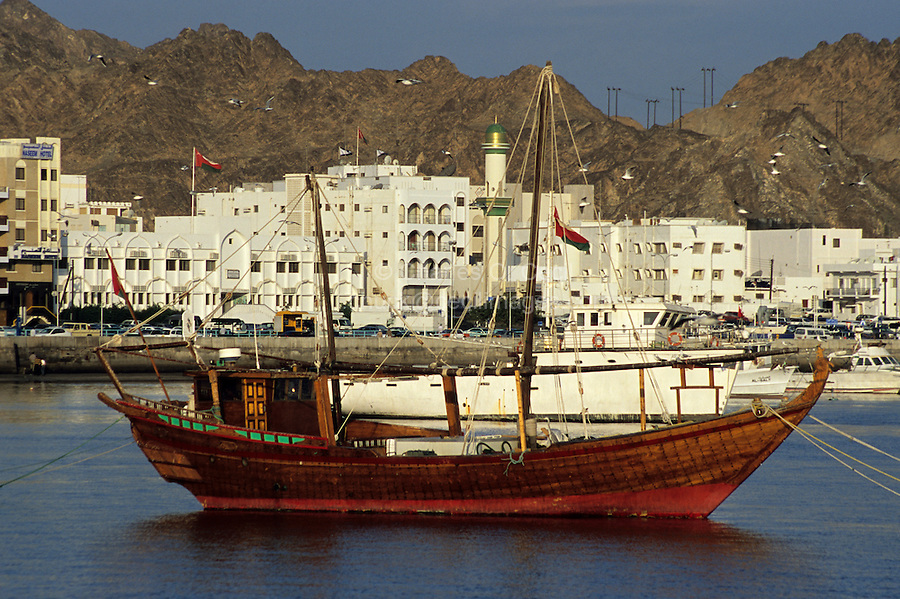 Mutrah, Oman.  An Arab dhow and traditional waterfront architecture denote the harbor of Mutrah, commercial port for Oman's capital, Muscat.  Oman is the legendary home of Sindbad the Sailor.  Behind the town are chocolate-brown ophiolites, a metamorphic, igneous rock.