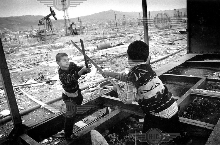 ©Heidi Bradner/Panos Pictures..Two boys, refugees from the war in Nagorno-Karabakh, play at sword-fighting using sticks of wood in an abandoned and polluted oil field near the shack where they live in the suburbs of Baku, capital for Azarbaijan...Pools of stagnant and noxious oil by-products seep through the flat landscape from old wells and industry.