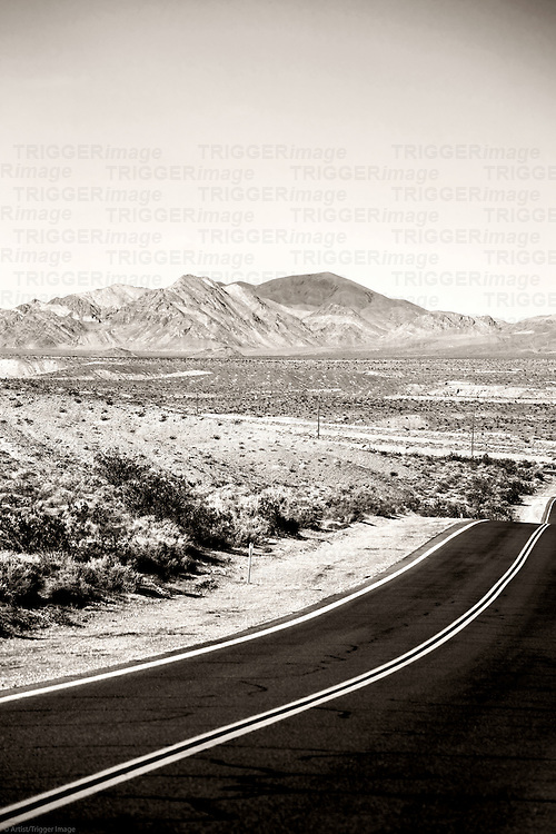 A road runs through the Mojave Desert to mountains between Baker and Shoshone.