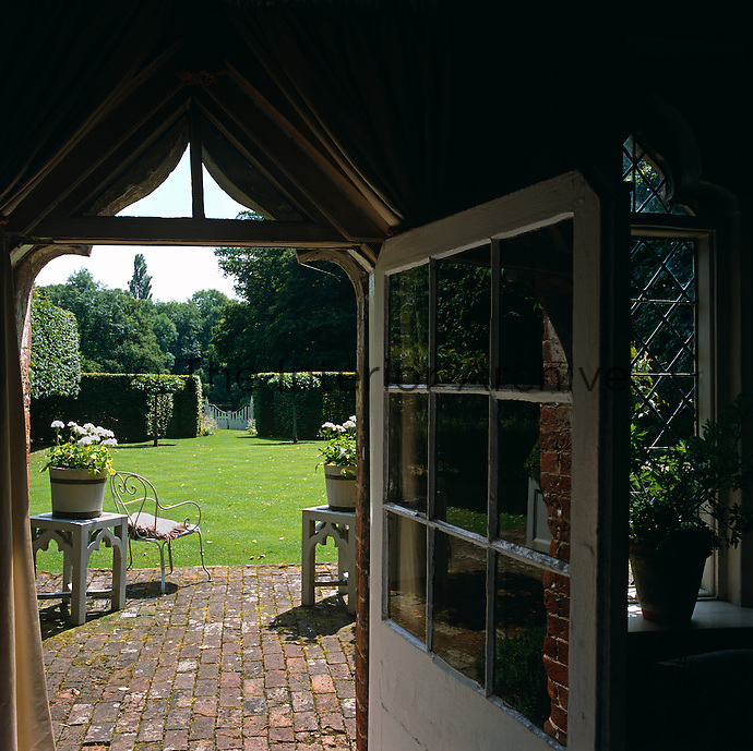 View of the garden from an open glass-paned door to the Tudor folly