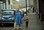 Mother and son in working class area of Hull Humberside circa 1985 Hessle Road area. The Lord Line building - former trawler company distinctive offices near the Albert Docks in background. This may be either Flinton Street or Gillett Street. If you know let me know please. <br />