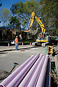 Workers excavate a trench while reclaimed water pipes lie in the foreground. The cities of Palo Alto and Mountain View are jointly constructing a reclaimed water pipeline to carry recycled water from the Palo Alto Regional Water Quality Control Plant to customers along East Bayshore Parkway and Mountain View's North Bayshore area.