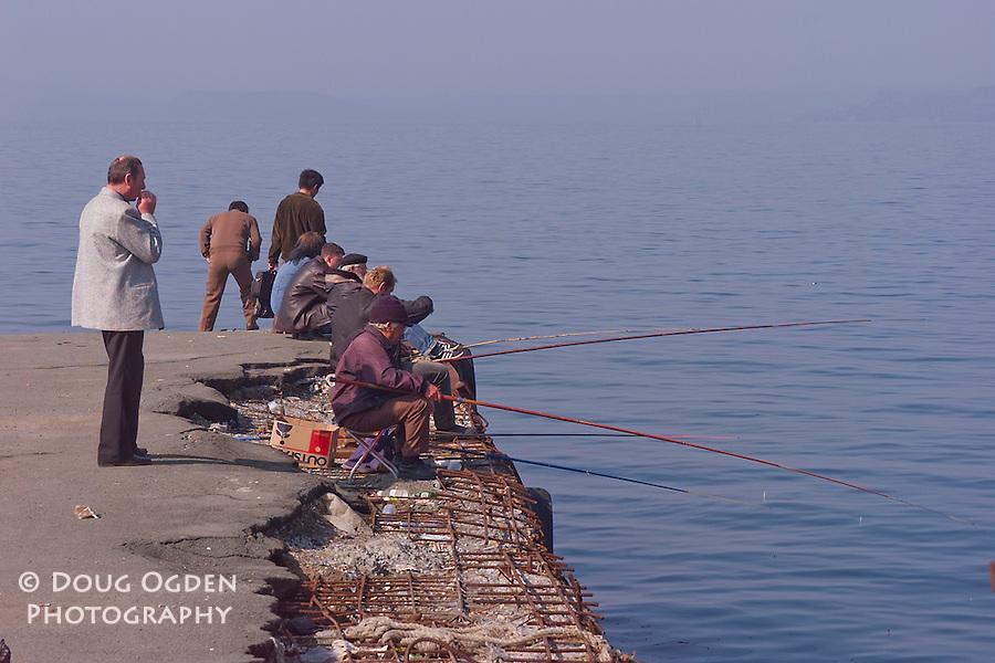 Fishermen off a decaying pier at the Sportivnaya Harbor, Vladivostok, Russia