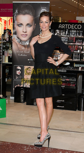 TARA PALMER TOMKINSON.launches Artdeco cosmetics at Fenwicks, Brent Cross Shopping Centre, London, England, UK, April 30th 2010..photocall full length dress black pearl necklace platform white print pattern patterned shoes hand on hip TPT.CAP/ROS.©Steve Ross/Capital Pictures.