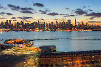 The Manhattan skyline during morning twilight as viewed over the Hudson River looking east from Weehawken, New Jersey.  The eastern sky and clouds were accented with tinges of orange that began to show in the hour before sunrise.