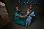 Rebecca Achol Atem dresses her 5-year old daughter Saloma Nyandeng early in the morning on April 13, 2017, as she gets the girl ready to go to an early childhood development center in Panyagor, a town in South Sudan's Jonglei State. <br /> <br /> The Lutheran World Federation, a member of the ACT Alliance, is helping families in the region, which is torn by both war and drought, to educate their children, with a special focus on insuring that girls enter and remain in school.