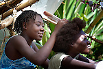 Mirlim Lectoa braids the hair of her sister Sandra in the southern Haitian village of Castillan.