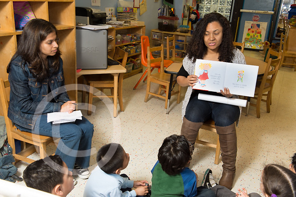Education preschool 4-5 year olds female teacher reading to small group observed by SEIT who is taking notes