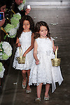 Flower girls sprinkle flower petals onto runway during the Atelier Pronovias 2014 collection fashion show by Pronovias, at St. James' Church in New York City, on November 12, 2013.