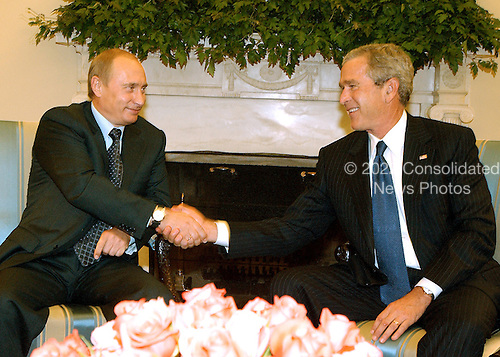 Washington, D.C. - September 16, 2005 -- United States President George W. Bush, right, welcomes President Vladimir Putin of Russia to the Oval Office in the White House in Washington, D.C. on September 16, 2005 for bi-lateral talks..Credit: Ron Sachs / CNP