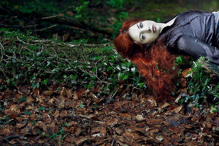 A girl with red hair laying alone on a log covered in vines beside autumn leaves