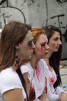 3 female participants in the zombi walk in may in prague europe, photographed in profile sitting next to eachother, wearing white t-shirts with blood on them.