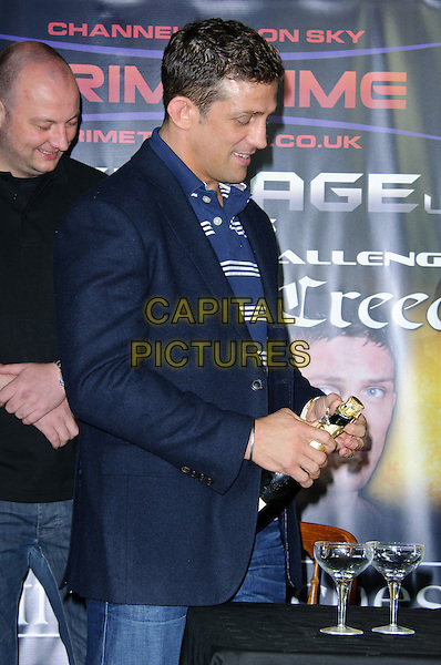 Alex Reid.Alex Reid makes announcement about forthcoming Cage Fight, London, England..July 20th, 2011.half length blue  white striped stripes top jacket black glasses side table champagne bottle profile .CAP/CJ.©Chris Joseph/Capital Pictures.