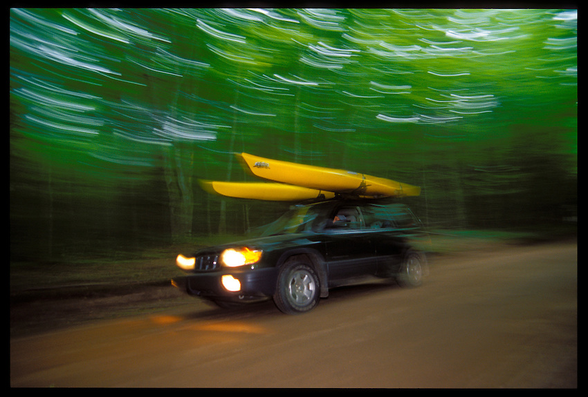 A SUBARU FORESTER CARRYING TWO SEA KAYAKS CRUISES ALONG ALGER COUNTY HIGHWAY 58 IN THE PICTURED ROCKS NATIONAL LAKESHORE BETWEEN MUNISING AND GRAND MARAIS.