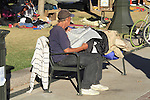 Homeless man reads newspaper at Occupy Wall Street demonstration, Denver, Colorado. .  John offers private photo tours in Denver, Boulder and throughout Colorado. Year-round Colorado photo tours.