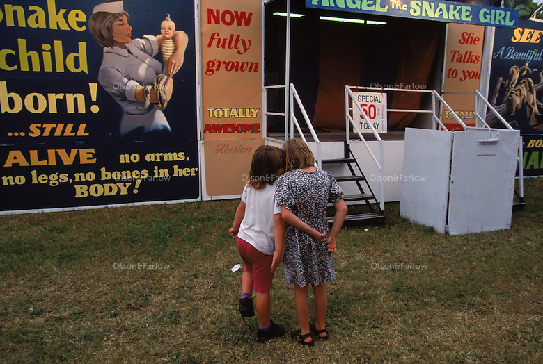 Two girls stand outside a side show at the county fair that features oddities of nature. Freak shows were popular in the mid 19th to 20th centuries and were associated with carnivals and circuses.