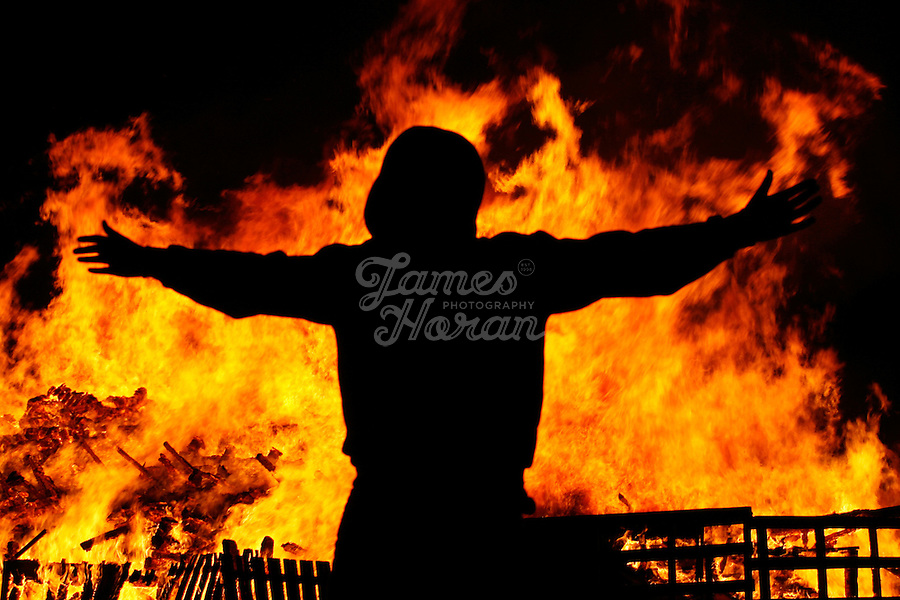 A Youth celebrates as the Irish flag is burned on a giant bonfire made from pallets and old tyres on a Loyalist estate, Belfast Northern Ireland.The bonfires which are seen by the Protestant community as a celebration of loyalist culture in the province are lit on the eve of 12 July, which is the anniversary of the Battle of the Boyne at which the Protestant King William of Orange defeated the Catholic King James in 1690. The festival causes outrage in the nearby republician and Catholic areas of the city.