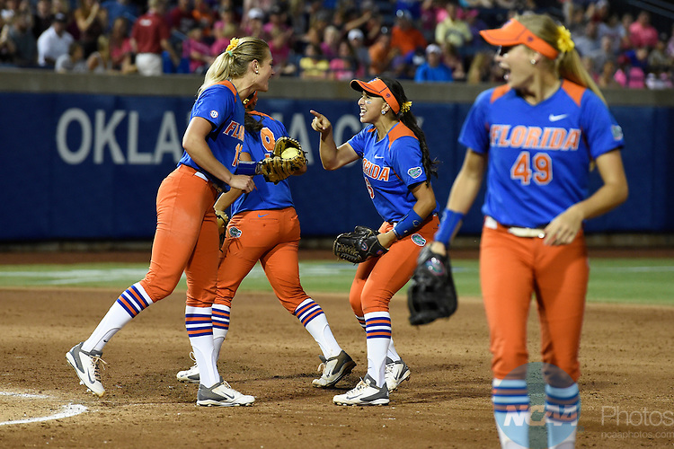 02 JUNE 2014:   Katie Medina (6) and Hannah Rogers (13) of the University of Florida celebrate after a double play against the University of Alabama during the Division I Women's Softball Championship held at ASA Hall of Fame Stadium in Oklahoma City, OK.  Florida defeated Alabama 5-0 in Game One.  Jamie Schwaberow/NCAA Photos
