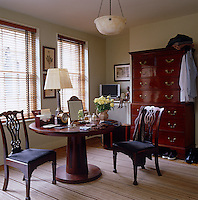 The masculine dressing room is furnished with a mahogany table by Philippe Hurel, an 18th century English chest-on-chest and an alabaster light fixture by Robert Kime