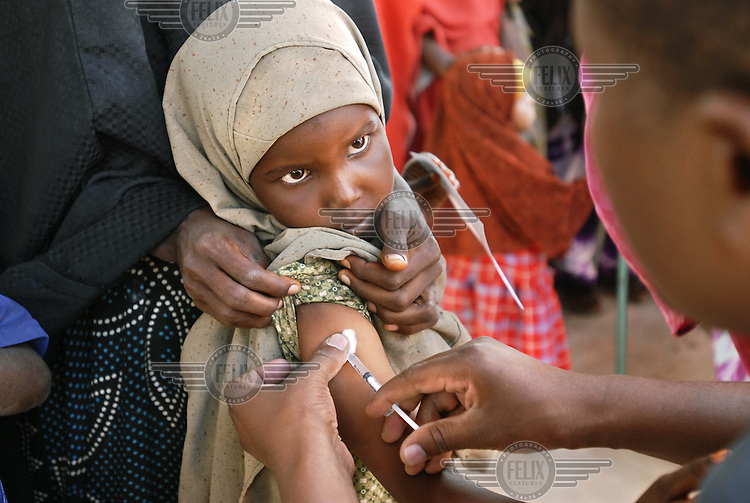 A young girl is administered a vaccination against measles by medical staff from Medecins sans Frontieres (MSF).  In a population weakened by the effects of drought, the outbreak of measles is a threat.  The severe drought has extended across East Africa after the rainy season expected in October 2005 failed to arrive, continuing a decade of low rainfall...