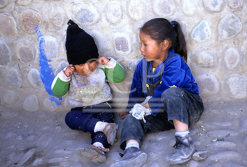 Paucartambo, Peru. Two children sitting at the  foot of a wall.
