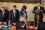 Sen. Charles Schumer (D-NY), President Barack Obama, and First Lady Michelle Obama, from left, bow their heads during the invocation at the Inaugural Luncheon in Statuary Hall in the U.S. Capitol on Monday, January 21, 2013 in Washington, DC.