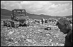 The manager of the Oaxaca, Mexico city dump watches as the bulldozer moves the old garbage out of the way for the neverending line of incoming trucks. A plastic collector waits to pick through the load to earn his wages for the day.