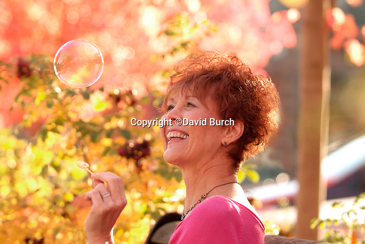Redheaded woman blowing bubbles outside, in a park