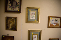 Framed paintings and photographs hang on a wall in a Salvation Army thrift store in Pendleton, Oregon, USA.