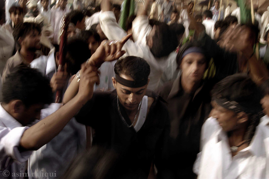 bari imam shrine, islamabad, pakistan 2004: young men accompanying an offering of decorative drapes and flowers for bari imam's shrine dance to the music of drums and attempt to achiece a state of ecstacy<br />