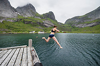 Female hiker jumps off jetty into cold fjord water at Kirkefjord, Moskenesøy, Lofoten Islands, Norway