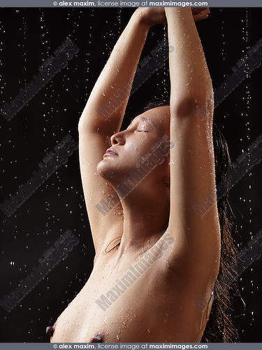 Young naked woman stanging under the raining water