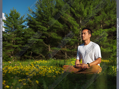 Toronto Shaolin school instructor Dao meditating outdoors during sunrise in the nature, sitting cross-legged in green outdoor summer nature scenery. Buddhist meditation. Instructor Shi Chang Dao, Toronto Shaolin Temple STQI.