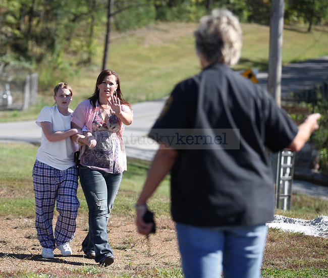 Officer Michelle Dunaway yells at her mom, officer Kay Chambers, to stop and not hurt the captured escapee Amanda Driggers and she gets brought back into the yard of Three Forks Regional Jail. Dunaway found her hiding in a ditch that other officers had sped by. Photo by Britney McIntosh