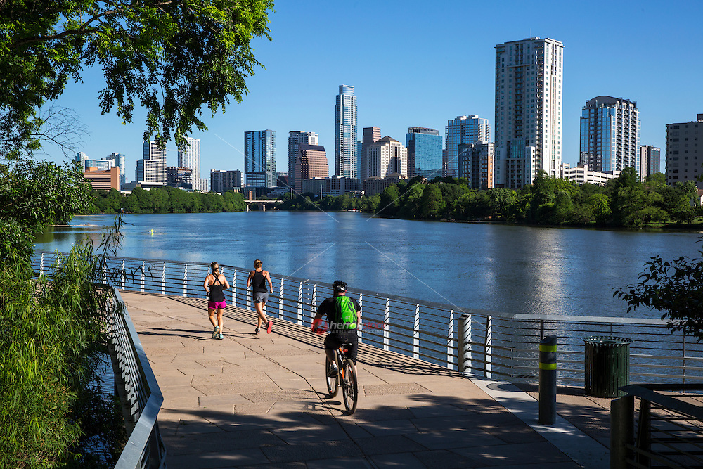 Runners and bikers exercise to maintain a healthy lifestyle on the Lady Bird Lake Hike and Bike Trail in downtown Austin on a beautiful summer day, fit healthy lifestyle, inset Austin Skyline - stock image.