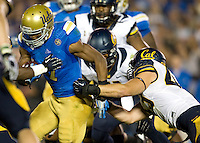 California defenders tackle Devin Fuller of UCLA during the game at Rose Bowl in Pasadena, California on October 12th, 2013.   UCLA defeated California, 37-10.