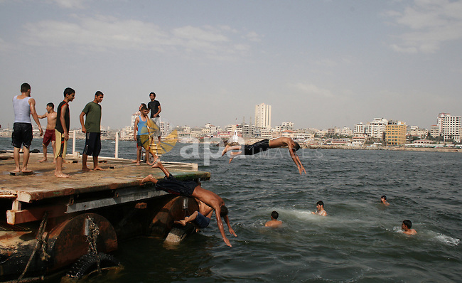 Palestinians enjoy in Gaza port on June 12, 2010. Gaza has been mired in poverty for decades, but the embargo by Israel deepened the misery, erasing tens of thousands of jobs and preventing repair of damage from the Israeli offensive. Photo by Mustafa Alashqar