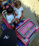 BABYLON, NY-MONDAY, AUGUST 13, 2007: Emma Valle,4, of Babylon gives Justin Alvarez,4 of Deer Park, instructions on seatbelt use in her toy Jeep before taking him for a ride at Argyle Lake Park in Babylon on Monday August 13, 2007. <br /> Newsday / Jim Peppler