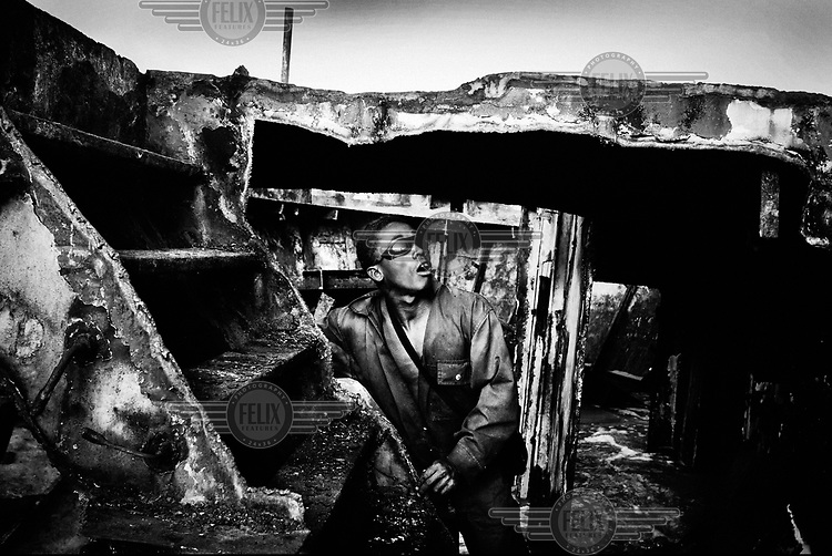 A man looks up from within the hold of a wrecked ship that he and his colleagues are attempting to dismantle. In 2011 Indian scrap merchants signed a deal with the government of Madagascar that gave them rights over the salvage of the many wrecks off Port Dauphin, on the island's southernmost tip. Labourers for this heavy work were easily found among the unemployed fishermen of the region. Armed with metal cutters, hammers and chisels they cut the rusting hulks into movable pieces that are shipped in containers to ironworks in India. The men earn GBP 1.00 per day for this backbreaking work. The boats are dismantled up to the waterline leaving a piece of the wreckage remains on the seabed. Groups of fishermen still try to recover the remaining metal, they dive with snorkels and hacksaws to the wreckage as they can earn GBP 75.00 per ton of metal they drag to the warehouse.