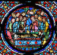 The 12 apostles, with expressions of grief, lower the body of Mary into her tomb, one swings incense while an angel descends on the scene from above. The Entombment of the Virgin, from the Glorification of the Virgin stained glass window, in the nave of Chartres Cathedral, Eure-et-Loir, France. This window depicts the end of the Virgin's life on earth, her dormition and assumption, as told in the apocryphal text the Golden Legend of 1260. Chartres cathedral was built 1194-1250 and is a fine example of Gothic architecture. Most of its windows date from 1205-40 although a few earlier 12th century examples are also intact. It was declared a UNESCO World Heritage Site in 1979. Picture by Manuel Cohen