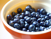 Summer blueberries in a red bowl.