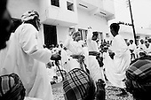 Salalah, Oman.July 2001..Family and friends come out to dance, sing and celebrate the marage of a Omani man in front of his home. The wife will be brought to the home the following day.