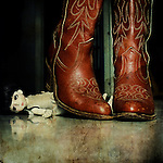 a pair of cowgirl boots over a little doll